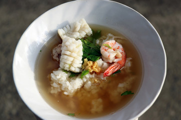 rice congee mixed with Shrimp, squid and pork, Garnish with coriander and preserved of Celery. it is a broth or porridge made from rice in the white bowl.