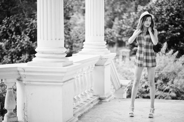 Amazing long legs with hig heels girl wear on hat posing near vintage building columns.