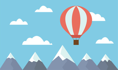 A view of a large and hot air balloon flying between clouds in a blue sky above mountain peaks