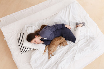 young girl in a blue pajamas sleeps on a big white bed with a gingercat. Healthy day sleep. Top view