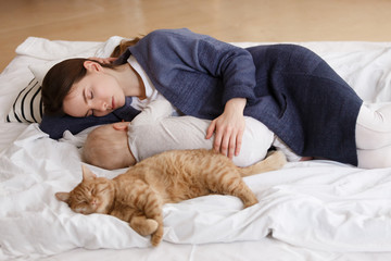 young caucasian mother sleeps together with baby boy in the afternoon in a bed together with a ginger cat. Focus on woman, top view. Healthy day sleep.