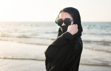 Portrait of a woman in abaya on the beach