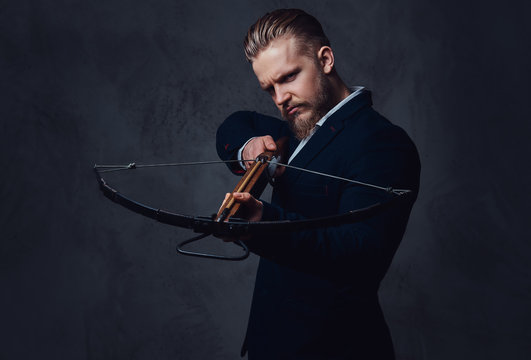 A man dressed in a suit holds crossbow.