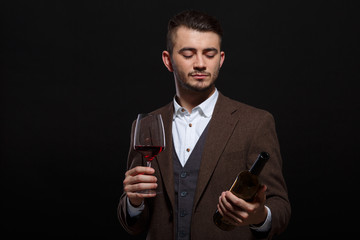 Fashionable white man with a glass and a bottle of wine in hands on a black background