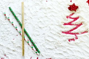 Red Christmas tree painted on snow and holiday straws for drinking. Top view, copy space