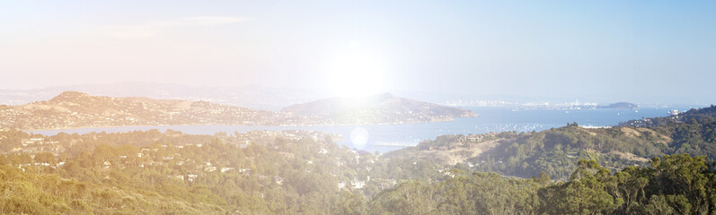 Sunlight shines over a panoramic landscape of hills and water in the San Francisco bay area in California