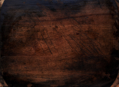 Dark rustic wooden cutting board stained with squid ink.