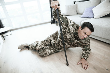 A man in uniform is lying on the floor. He fell with a crutch in his hand. It hurts. He is in the large bright living room of his modern apartment.