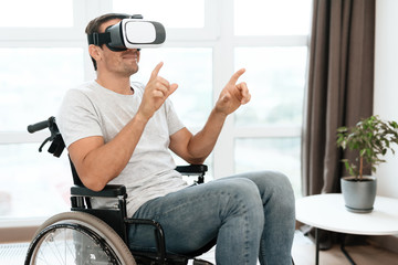The disabled person is sitting in a wheelchair in virtual reality glasses. He spread his hands to the sides. He sits in his large bright living room and enjoys virtual reality.