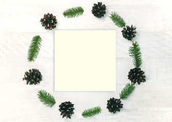 Christmas wreath made of pine cones and sprigs fir.on the white wooden background. Natural decor ornament for holiday card. Xmas card