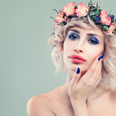 Beautiful Lady Fashion Model with Roses Flowers and Green Leaves in her Hair. Cute Woman with Blonde Bob Hairstyle and Manicured Hand