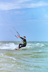 Man riding a kite surfing on the waves in the summer.