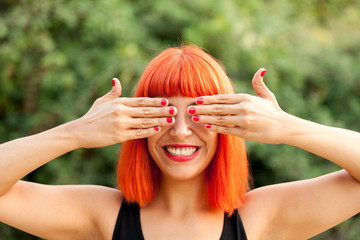 Red haired woman covering her eyes in a park