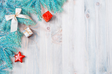New Year and Christmas background. Christmas toys, blue fir tree branches on the wooden background. New Year still life
