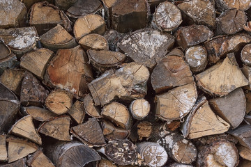 Wood chopped firewood stacked on the stack. Woodpile of cut trees in the lumberyard. Background and texture with space for text or image. Fire wood prepared for winter