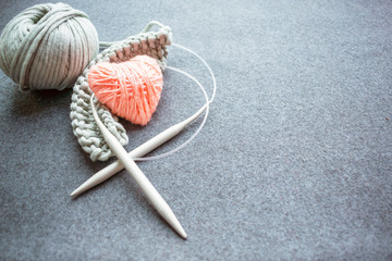 Set for knitting: knitting needles, corded cotton yarn, started knitting and pink heart of thread on dark felt background. Grey Yarn ball and heart shape Yarn with knitting needles