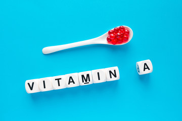Red capsules in the white spoon and the word vitamin A from white cubes with letters on a blue background. healthy and medical concept. retinol, retinal, retinoic acid