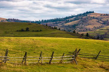 wooden fence on grassy rural hill in late autumn sunny day. beautiful scenery in mountainous area