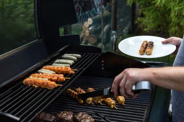 Mann legt das fertige Fleisch vom Gasgrill mit einer Grillzange auf einen Teller