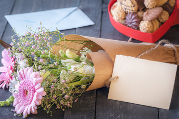 Flower bouquet and a blank label - Celebration theme image with a lovely bouquet of flowers wrapped in brown paper with a tag attached to it, surrounded by a box of cookies and an envelope.