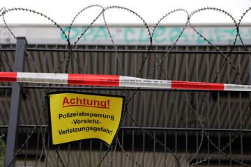 Zaun mit Polizeiabsperrung und NATO-Stacheldraht