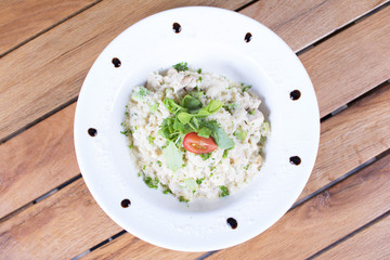 Fragrant Pilau/Pulav / pilaf /pilaf, fried rice with meat and vegetables on a white plate. Isolated on a wooden table.