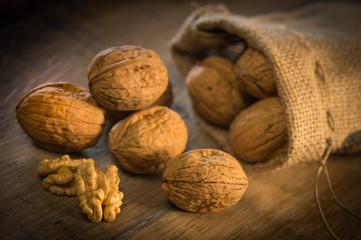 Walnut kernels and whole walnuts on rustic old oak table