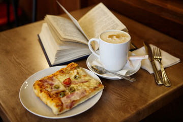Cup of coffee with a pizza on the table in the cafe