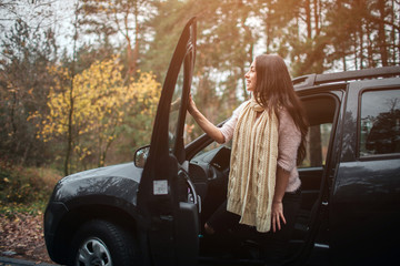 Long-haired brunette on the auto background. A female model is wearing a sweater and a scarf. Autumn concept. Autumn forest journey by car