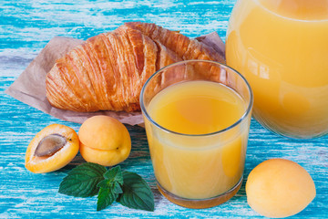 Apricot juice and croissant with golden crust