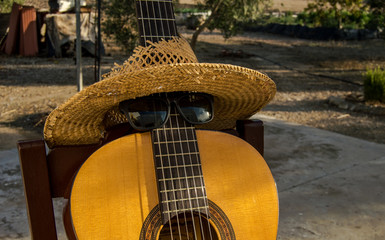 Spanish guitar dressed as a person with sunglasses and hat in a ranch.