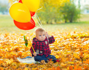 The image of a little child with a bunch of balloons in their hands in yellow autumn park