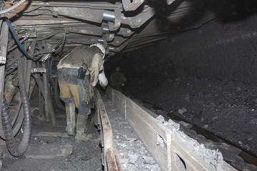 Miners are in the close tunnel of the underground mine. Ukraine, Donbass