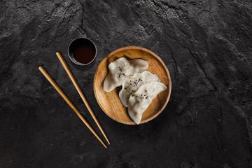 Plate of Asian gyoza dumplings with soy sauce on black slate stone.
