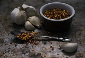 Red Pepper Flakes with Raw Garlic on a Dark Metal Background