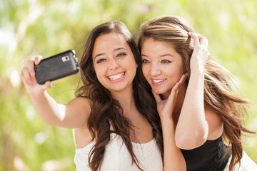 Two Attractive Mixed Race Girlfriends Using Their Smart Cell Phones For Selfie Outdoors