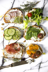 Sandwiches with fresh vegetables. Top view shot on white marble pattern background.