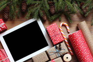 Tablet and Christmas gifts on a wooden table
