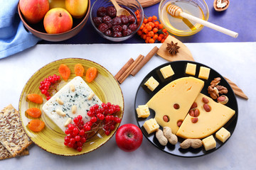 Cheese with mold, fruit, hard cheese with holes on a dark blue background, cheese on a black plate, fruits, nuts, honey, jam, Christmas dinner, multicolored background, retro style