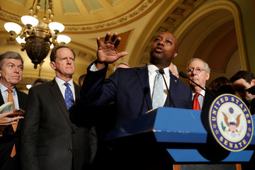 Sen. Tim Scott (R-SC), accompanied by Sen. Roy Blunt (R-MO), Sen. Pat Toomey (R-PA), and Senate Majority Leader Mitch McConnell, speaks with reporters following the party luncheons on Capitol Hill in Washington