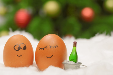 Funny lovely eggs in snow with bottle of wine
