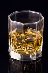 Octagon square glass with whiskey and ice cubes on the black background with reflections