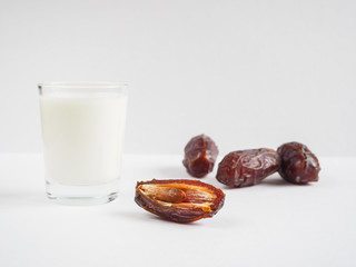 Date fruit and a glass of milk on a white background.