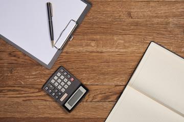 wooden background, tablet, pen, notebook, calculator