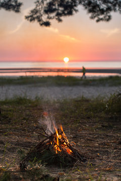 A small campfire on the shore against the backdrop of the setting sun and the silhouette of a man / small campfire from branches
