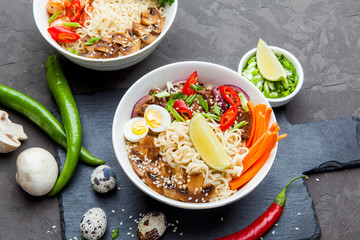 Noodles with beef meat, chili peppers and mushrooms in bowl on dark stone background.