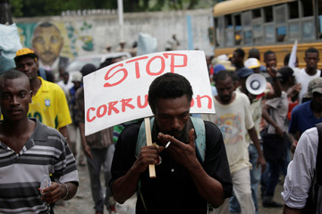 A protester smokes a cigarette as he marches carrying a placard during a demonstration against corruption in Port-au-Prince
