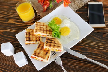 breakfast - sandwiches with corn on a wooden background on a background of scrambled eggs, orange juice, burlap, smartphone and flowers close-up