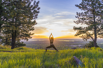 Girl does yoga at sunrise on grassy hill between two trees.
