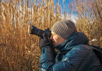 Closeup of photographer with digital camera outdoors. Young man photographs nature.